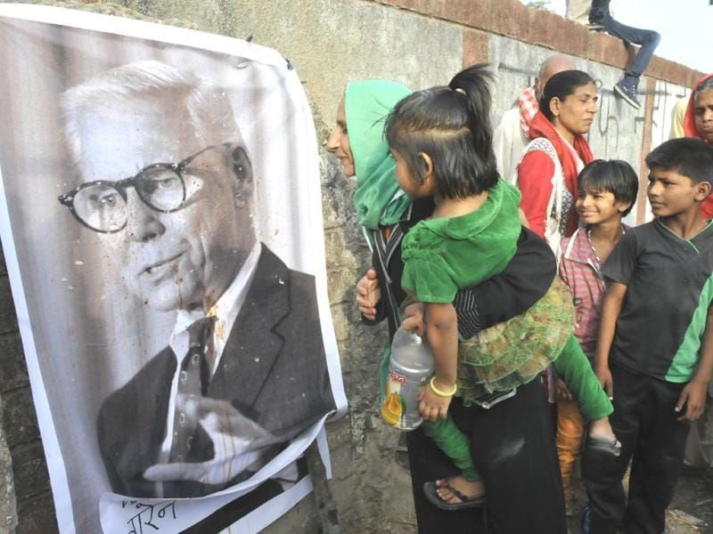 A woman spits at Warren Anderson's photograph that has been put up by activists in Bhopal on Friday. (Mujeeb Faruqui/HT photo)
