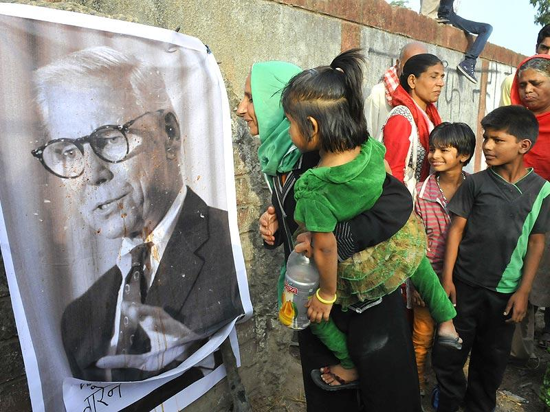 Bhopal gas tragedy victims spit on a poster of former chairman of Union Carbide Corporation Warren Anderson in Bhopal on Friday. (Mujeeb Faruqui/HT photo)