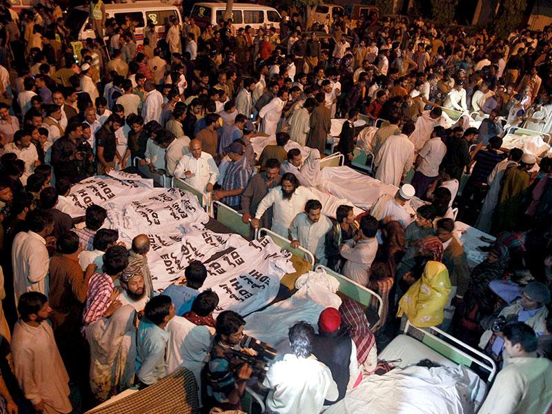 Relatives gather beside the covered bodies of victims who were killed in suicide bomb attack in Wagah border near Lahore. (Reuters Photo)
