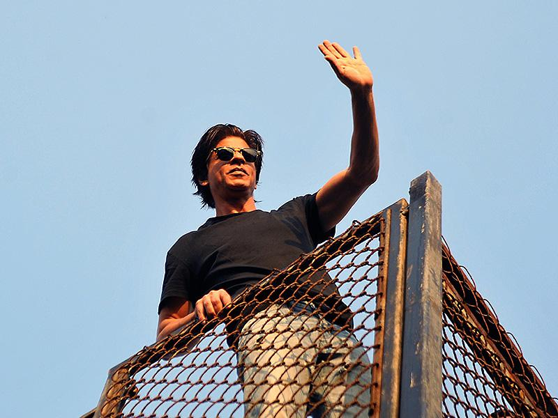 Shah Rukh Khan waves to fans during celebrations for his 49th birthday celebrations at his home in Mumbai on November 2, 2014. (AFP)