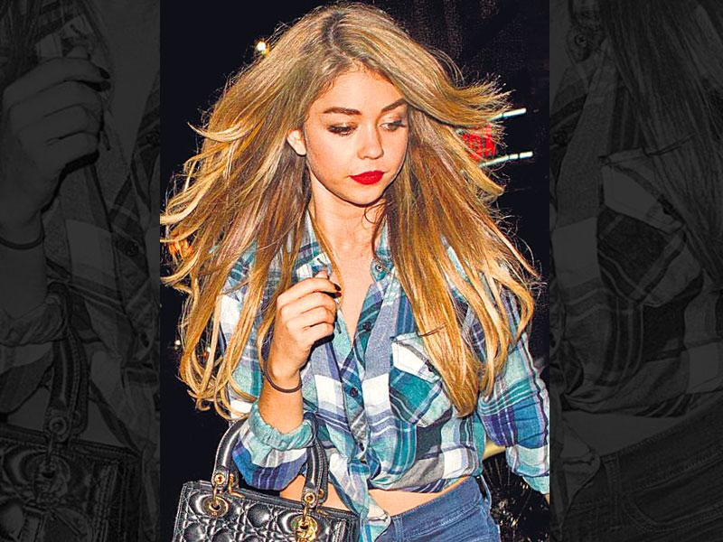 The plaid shirt is a rage this season, with a number of fashion forward ladies rocking the crossed horizontal and vertical bands in two or more colours on woven cloth. So girls, if you don't own a plaid shirt yet, steal from your boyfriend's closet. (Text: Aditi Caroli) | Glam it up: Who says you can't do glam in a plaid shirt? . Take cue from US TV star, Sarah Hyland, who shows off her waist in a knotted plaid shirt, teamed with skinny jeans and lace up knee-high boots. Leaving her hair loose, she adds instant drama with red hot lips.