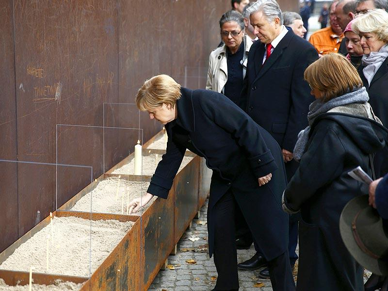 German Chancellor Angela Merkel places a candle to commemorate the victims who tried to escape across the former East German border after the church service during a ceremony marking the 25th anniversary of the fall of the Berlin Wall at a memorial in Bernauer Strasse in Berlin. (Reuters Photo)
