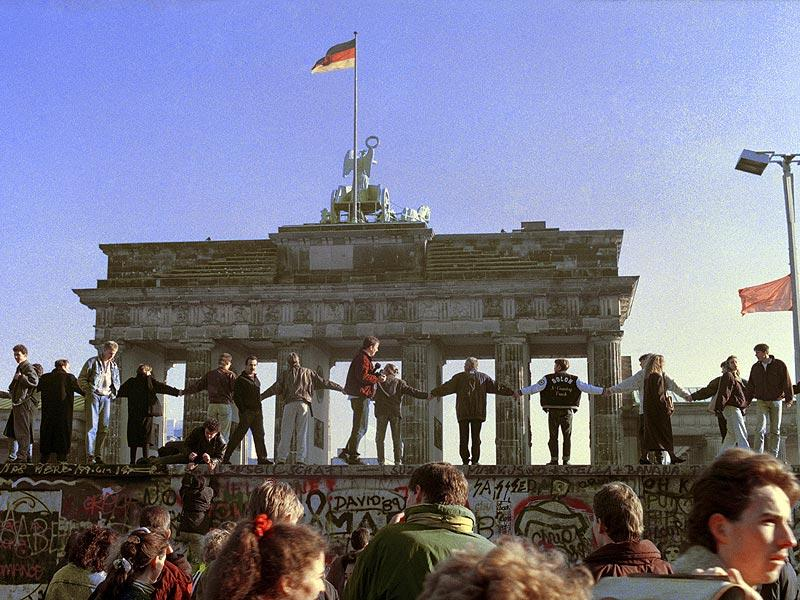 In this Nov. 10, 1989 file photo Berliners sing and dance on top of the Berlin Wall to celebrate the opening of East-West German borders. (AP Photo)