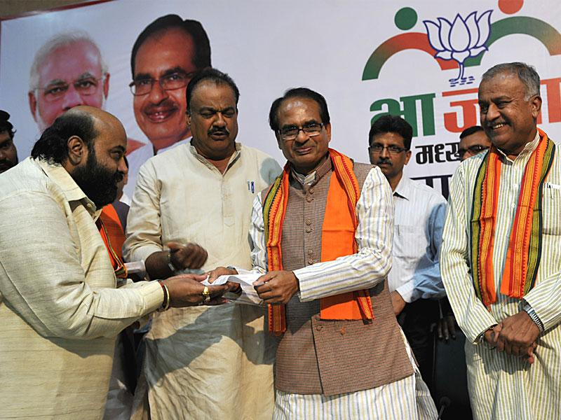 Chief minister Shivraj Singh Chouhan hands over BJP membership slip to Congress workers after they joined the BJP at the party office in Bhopal. (Mujeeb Faruqui/HT photo)