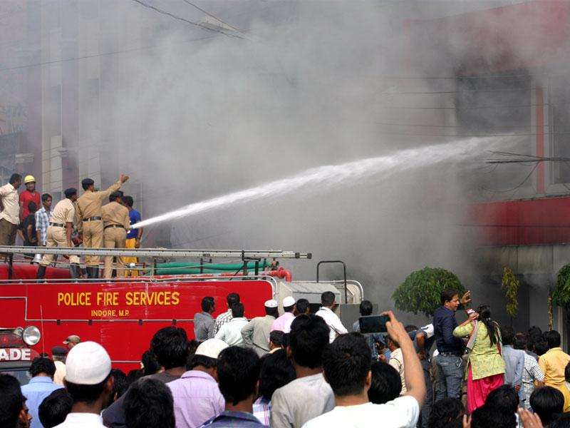 Firemen douse the flames after fire broke out at a two-wheeler showroom near Bhopal Talkies on Monday. (Bidesh Manna/HT photo)