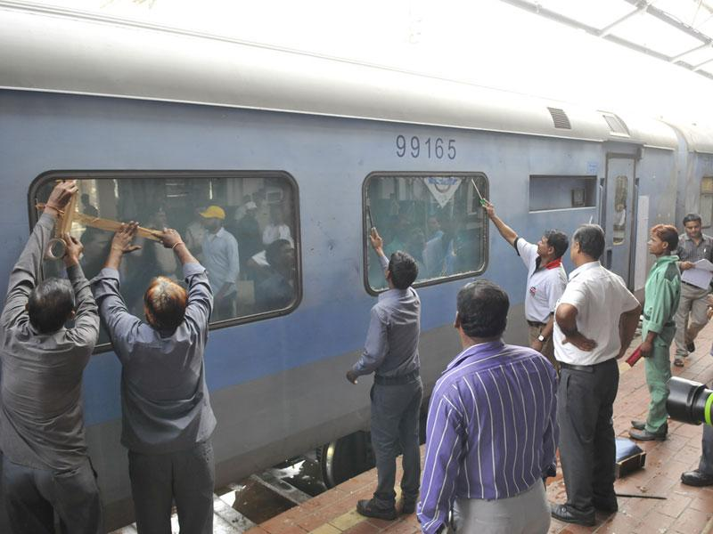Railway staff repairing the broken windows of Shatabdi Express in Bhopal after a mob attacked it in Gwalior. (Mujeeb Faruqui/HT photo)