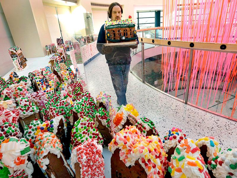 Chef Jon Lovitch carries the Cinnamon & Nutmeg Railroad station, one of his gingerbread house creations, for placement in his GingerBread Lane display, at the New York Hall of Science, in the Queens borough of New York. (AP photo)