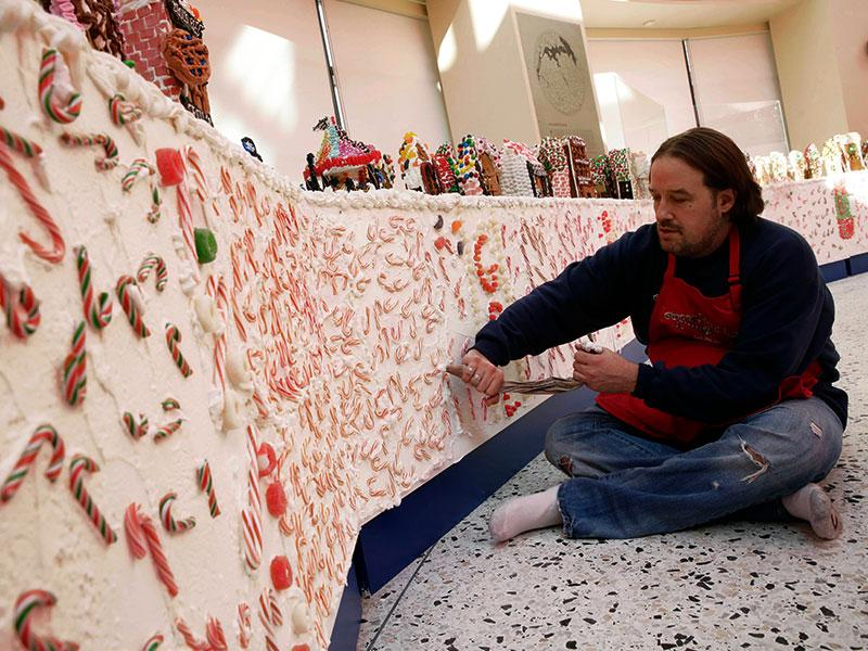 Chef Jon Lovitch uses a pastry bag of frosting as he prepares the border for his GingerBread Lane display, at the New York Hall of Science, in the Queens borough of New York. (AP photo)