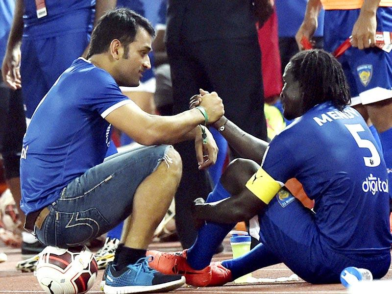Chennaiyin FC co owner MS Dhoni and a player Mendy after win over Mumbai City FC during the Indian Super League in Chennai. (PTI Photo)