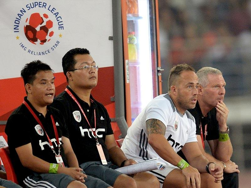 NorthEast United FC head coach Ricki Herbert (R) watches their Indian Super League (ISL) football match against Delhi Dynamocs FC with support staff in New Delhi. (AFP Photo)