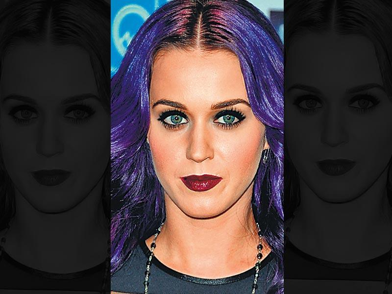 Singer Katy Perry goes for a dramatic look. She teams her plum lips with thickly-lined eyes. Her purple hair goes well with the statement look.