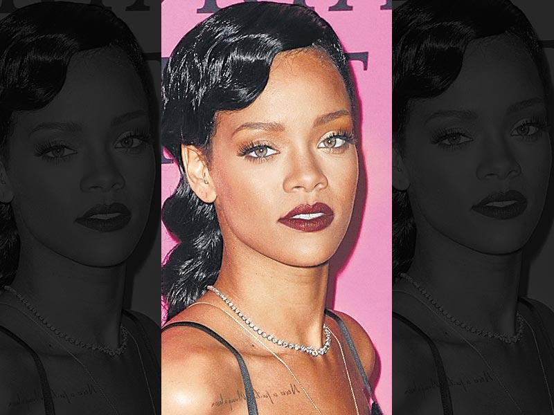 Pop star Rihanna rocks plum lips. Keeping the rest of the makeup neutral, she goes for dark lips with eyeliner and curled top lashes.