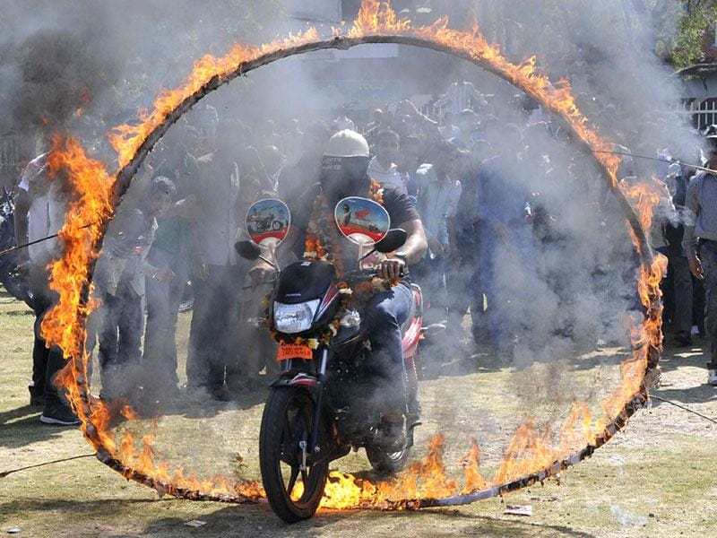 Magician Akash, son of Jadugar Anand, passes through a fire ring blindfolded on his motorcycle, in Bhopal on Thursday. (Mujeeb Faruqui/HT photo)