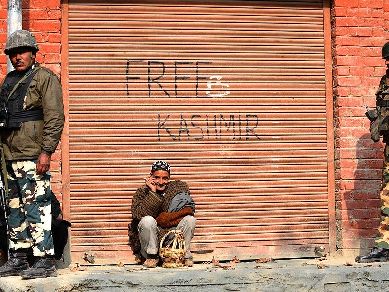 A Kashmiri resident leans against a shuttered storeroom for a smoke in Tral. As armed police in bullet-proof vests patrol the tense streets of India's only Muslim majority state, BJP candidate Avatar Singh forecast victory for his Hindu nationalist party in Kashmir's elections. (AFP Photo)