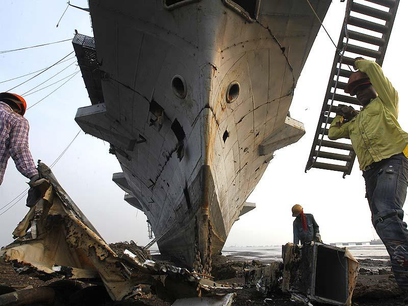 Workers climb to enter India's first aircraft carrier INS Vikrant to dismantle it at a ship-breaking yard in Mumbai. The iconic naval vessel, that was purchased from Britain in 1957, played a key role during the India-Pakistan war of 1971 and was decommissioned in 1997. (AP photo)