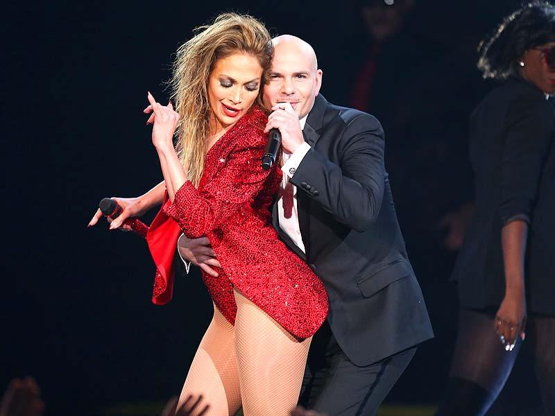 Jennifer Lopez (left) is embraced by Pitbull at the end of her performance at the 42nd annual American Music Awards at Nokia Theatre LA Live on Sunday, November 23, 2014 in Los Angeles. (AP)