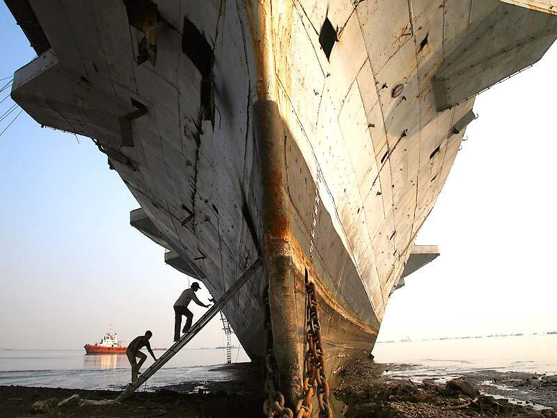 Workers climb to enter India's first aircraft carrier INS Vikrant to dismantle it at a ship-breaking yard in Mumbai. (PTI photo)