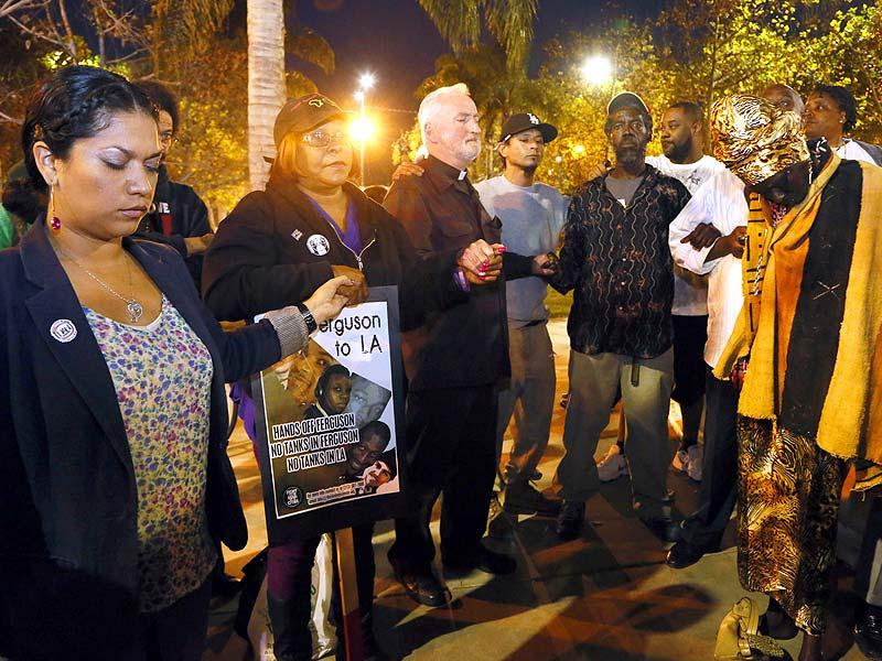 People hold hands in a prayer for peace at the Leimert Park area of Los Angeles after a grand jury's decision not to indict Ferguson police officer Darren Wilson in the fatal shooting of Michael Brown. (AP Photo)