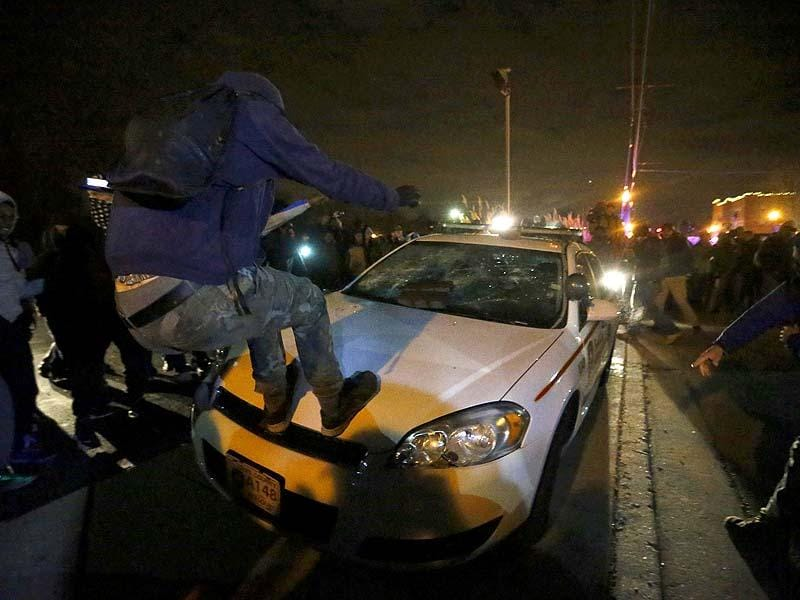 Protesters vandalize a car outside the Ferguson police department in Ferguson, Missouri. (Reuters Photo)
