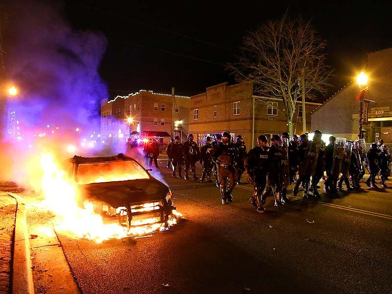 Police officers march by a burning police car during a demonstration in Ferguson, Missouri. (AFP Photo)