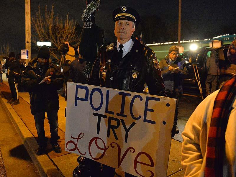 Retired captain Ray Lewis of the Philadelphia police department holds a sign outside the Ferguson police department in Ferguson, Missouri. (AFP Photo)