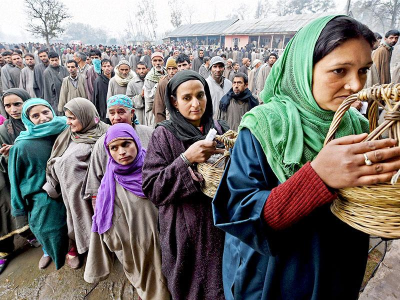 People wait in queues to cast their votes for Assembly elections at a polling station in Bandipora district of Jammu and Kashmir. (PTI photo)