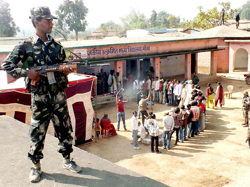 A security person stands guard outside a polling station during the first phase of Jharkhand assembly election in Latehar. (PTI photo)