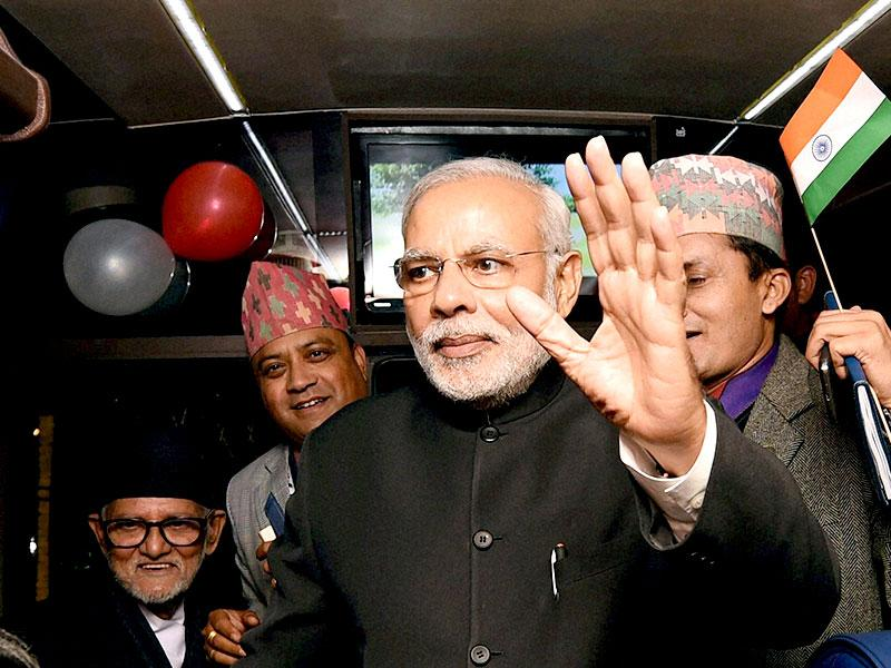 Prime Minister Narendra Modi waves to people inside a bus prior to flagging off its maiden journey from Kathmandu to New Delhi, in Kathmandu. (PTI photo)