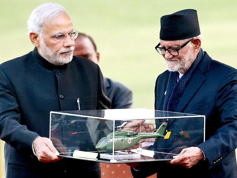 Prime Minister Narendra Modi presents the model of a chopper to his Nepali counterpart Sushil Koirala during the presentation ceremony of a chopper to Nepal army in Kathmandu. (PTI)