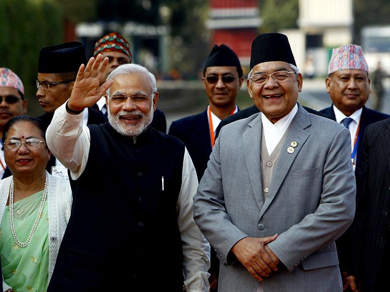 Prime Minister Narendra Modi waves to the media as he is received by Nepalese home minister Bam Dev Gautam upon arrival at the Tribhuwan Airport to attend the 18th summit of South Asian Association for Regional Cooperation (SAARC) in Katmandu. (AP photo)