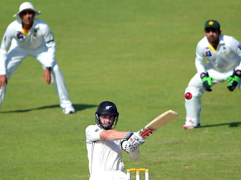 New Zealand batsman Kane Williamson (C) hits a shot as Pakistani wicketkeeper Sarfraz Ahmed (R) and teammte Younis Khan (L) look on during the third day of the third Test match at the Sharjah cricket stadium. (AFP Photo)