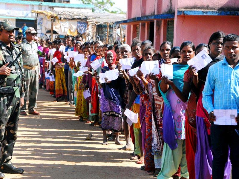 A security guard monitors proceedings as voters wait to cast their votes outside a polling station near Jharkhand capital Ranchi. (PTI file photo)