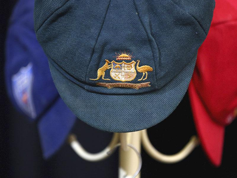 The Baggy Green cap of Phillip Hughes and his state cricket caps on a hat rack inside the Macksville High School Stadium during the funeral of Phillip Hughes in Macksville, Wednesday. (AP Photo)