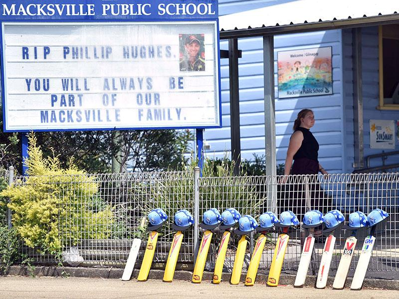 Cricket bats and helmets are lined up outside Macksville Public School hours before the funeral of Australian batsman Phillip Hughes in his home town Macksville on Wednesday. (AFP Photo)