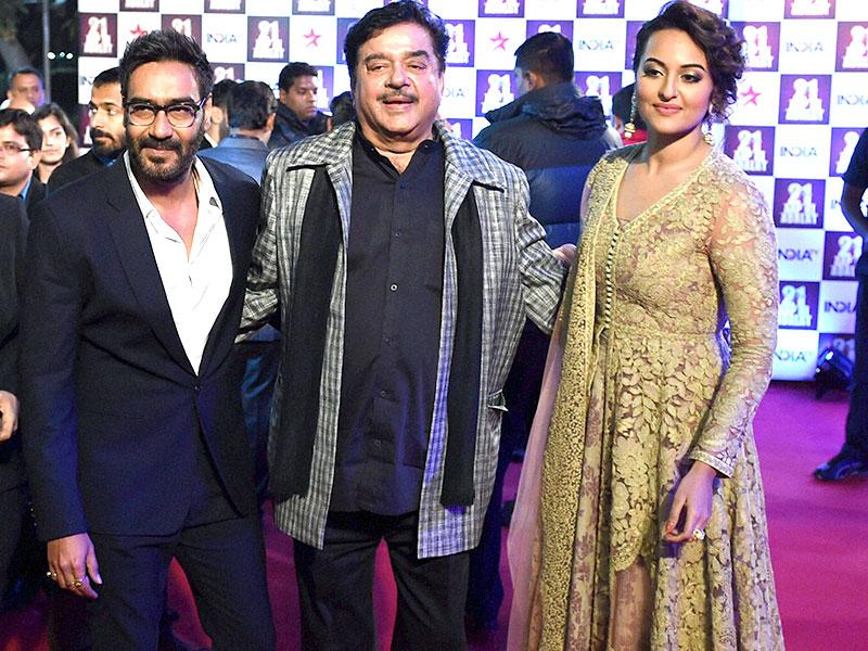 Ajay Devgan with actor-politician Shatrughan Sinha with her daughter Sonakshi Sinha on the red carpet, during the celebrations of a TV show, which has completed 21 years, in New Delhi on Tuesday. (PTI)