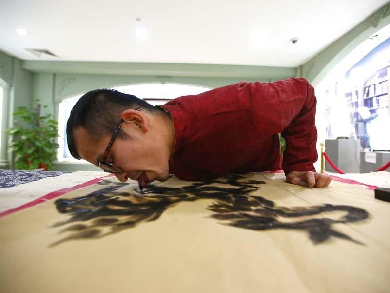 Folk artist Han Xiaoming demonstrates painting with his tongue in Hangzhou, Zhejiang province. (Reuters)