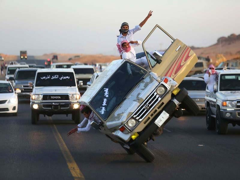 Saudi youths demonstrate a stunt known as 'sidewall skiing' (driving on two wheels) in the northern city of Tabuk, in Saudi Arabia. (Reuters)