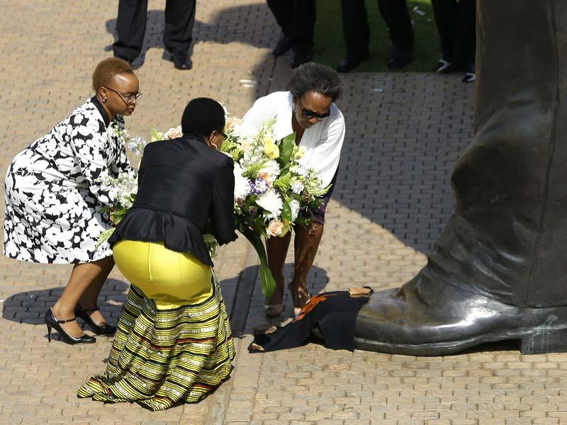 Nelson Mandela's widow Graca Machel, second left, and unidentified family members place a wreath to the 9 meter tall bronze statue of the late former South Africa President Nelson Mandela outside Union Buildings in Pretoria, South Africa on the first anniversary of his death. (AP Photo)