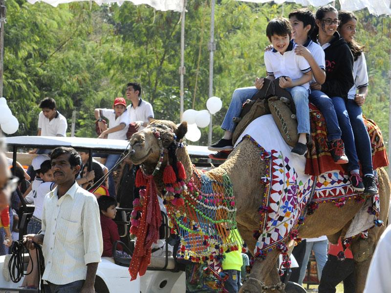Students enjoy a camel ride at a carnival for children at Daly College in Indore on Sunday. (Amit K Jaiswal/HT photo)
