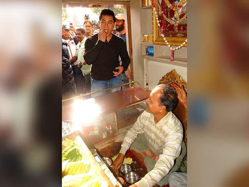 Bollywood actor Aamir Khan tries out banarasi paan during the promotion of his upcoming movie PK in Varanasi on Sunday. (PTI Photo)