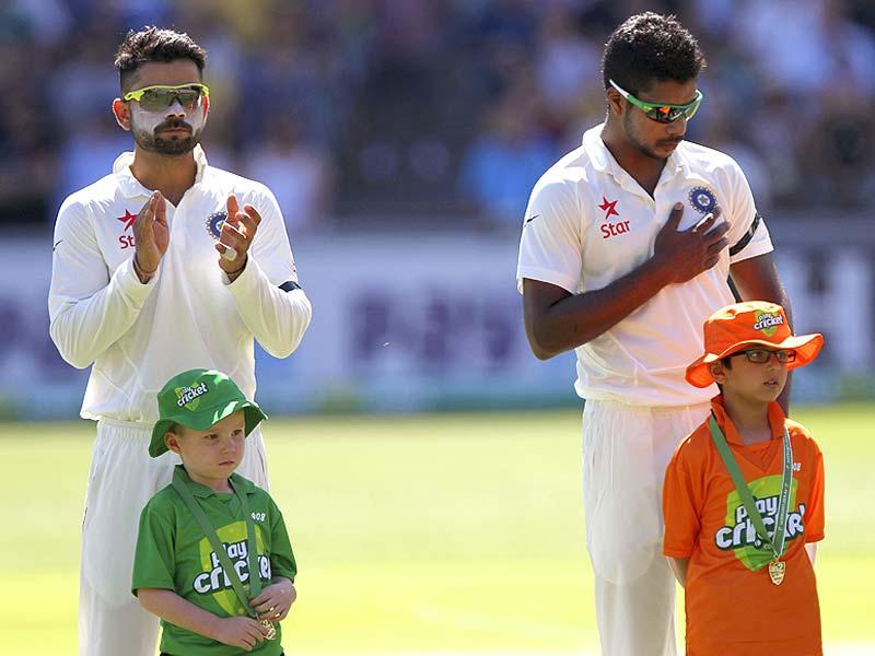 Virat Kohli and Varun Aaron wear black armbands as a tribute to Australian cricketer Phillip Hughes during a ceremony at the beginning of the first Test between Australia and India in Adelaide. (AP Photo)