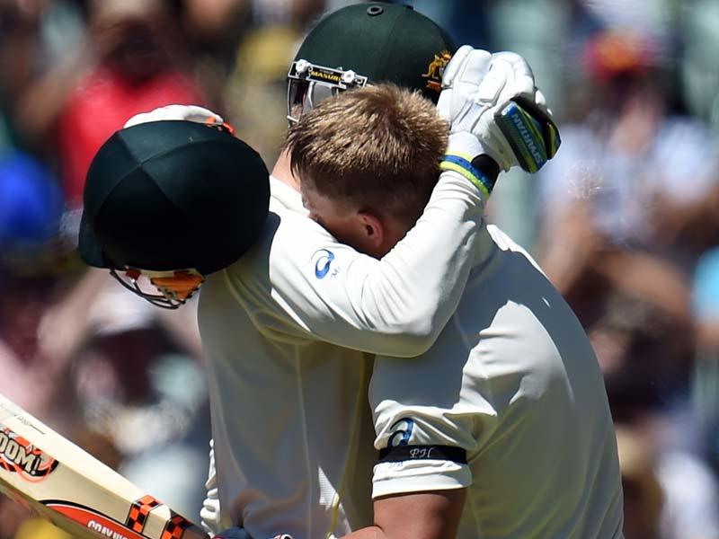 Australia's David Warner (R) hugs teammate Michael Clarke to celebrate his century on the first day of the first Test match between Australia and India at Adelaide Oval in Adelaide. (AFP Photo)