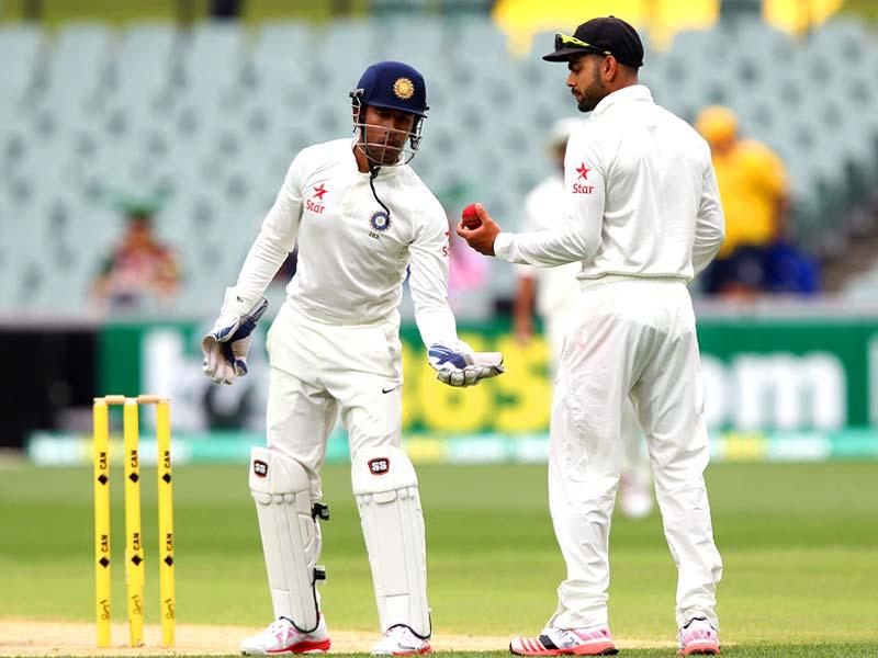 India's captain Virat Kohli passes the ball to wicketkeeper Wriddhiman Saha during the second day of their Test match against Australia in Adelaide. (AP Photo)