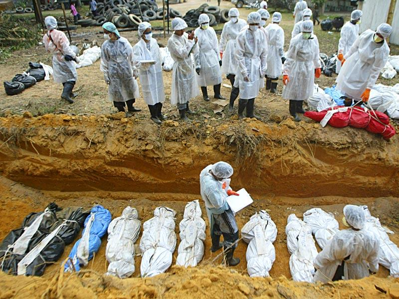 Thai health officials bury tsunami victims at a burial site in Takuapa, near Phuket, in January 2005. (Reuters)