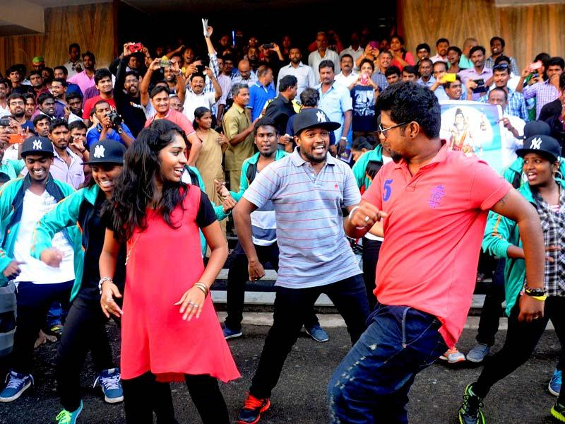 Fans of actor Rajinikanth dance during the release of his movie