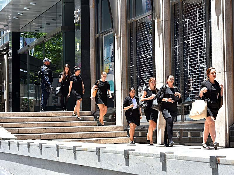 Armed police evacuate employees from the offices next to Lindt cafe in the central business district of Sydney. (AFP Photo)