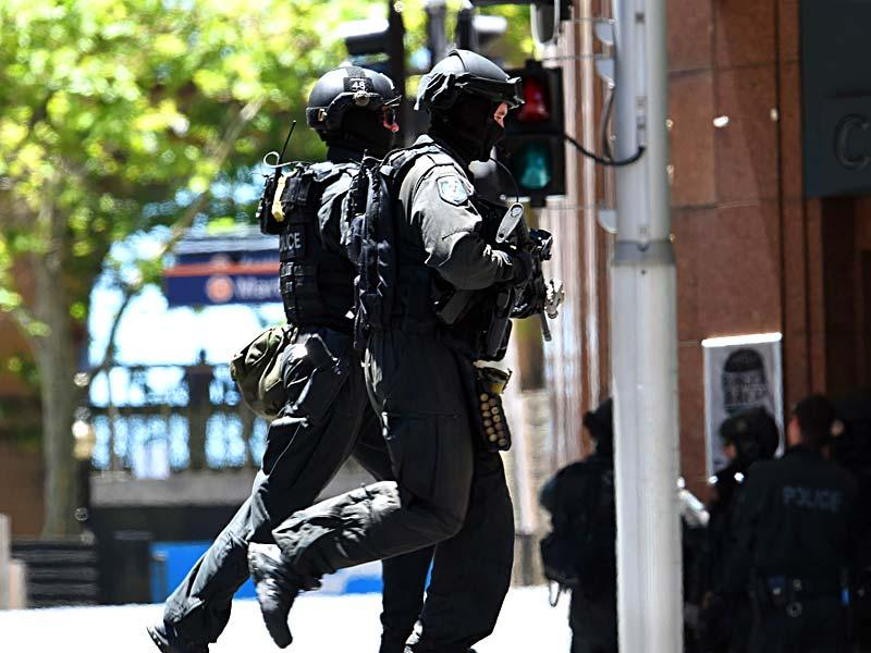 Armed police run toward the café where hostages were being held. (AFP Photo)