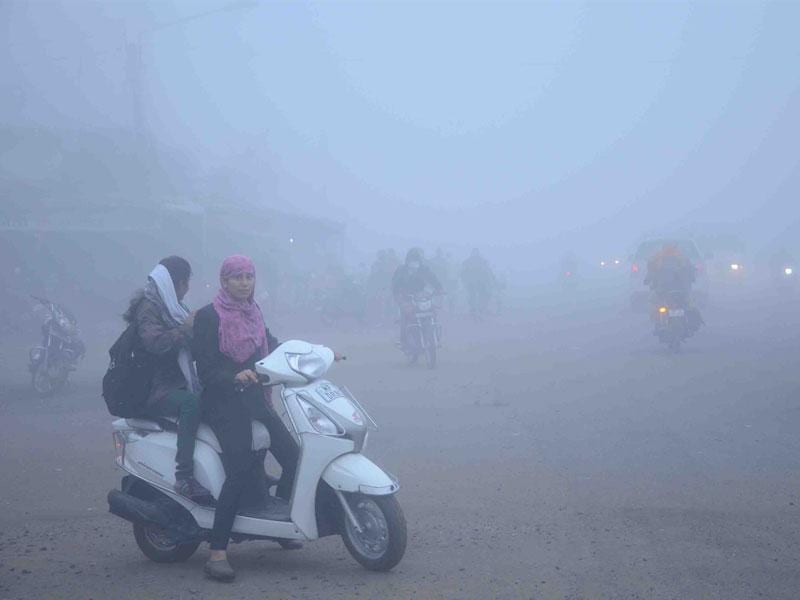 Commuters face a tough time as thick fog covers roads in Ujjain on Monday morning. (Sunil Magariya/HT photo)