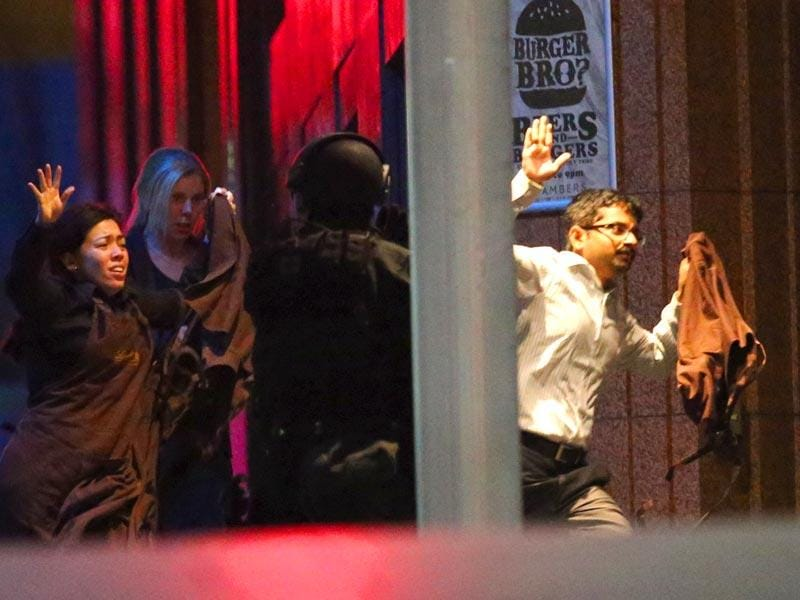 Hostages run past a police officer near Lindt Cafe in Sydney. (AFP photo)
