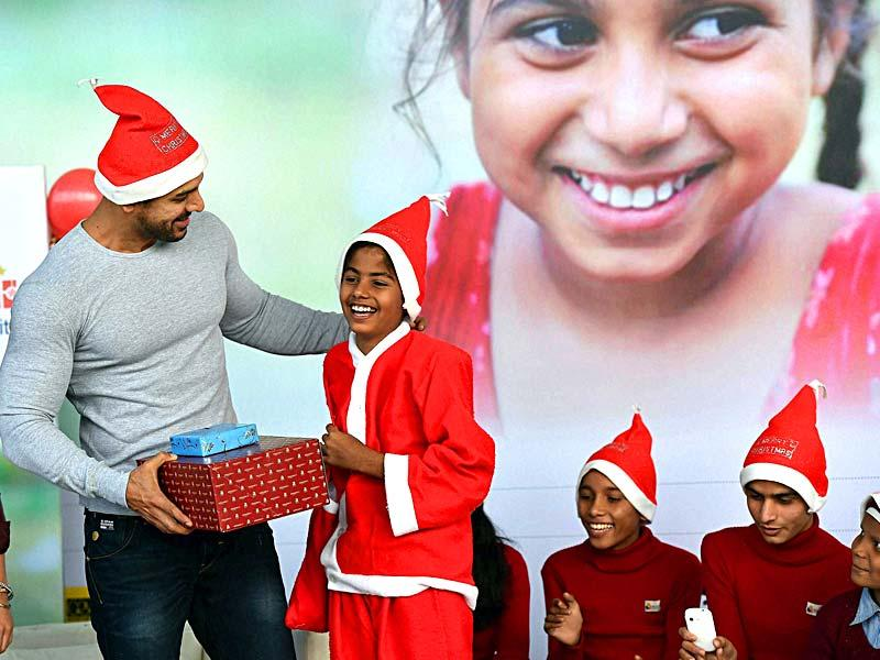 John Abraham, Brand Ambassador for Make a Wish Foundation, presents gifts to the underprivileged kids, in New Delhi. (PTI Photo)